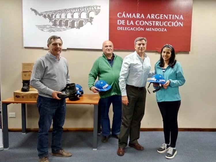 El Presidente de la CAC Delegación Mendoza, Ing. Marcelo Bargazzi, junto a los ingenieros Alejandro Cantú y Martín Garbuio, entregando casco y botines de seguridad a una alumna
